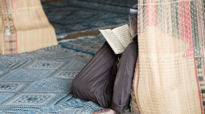 North African man reading in mosque