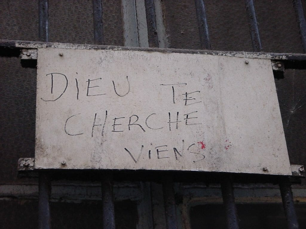 This handwritten sign on the barred window of a church in France reads, God is looking for you. Come.