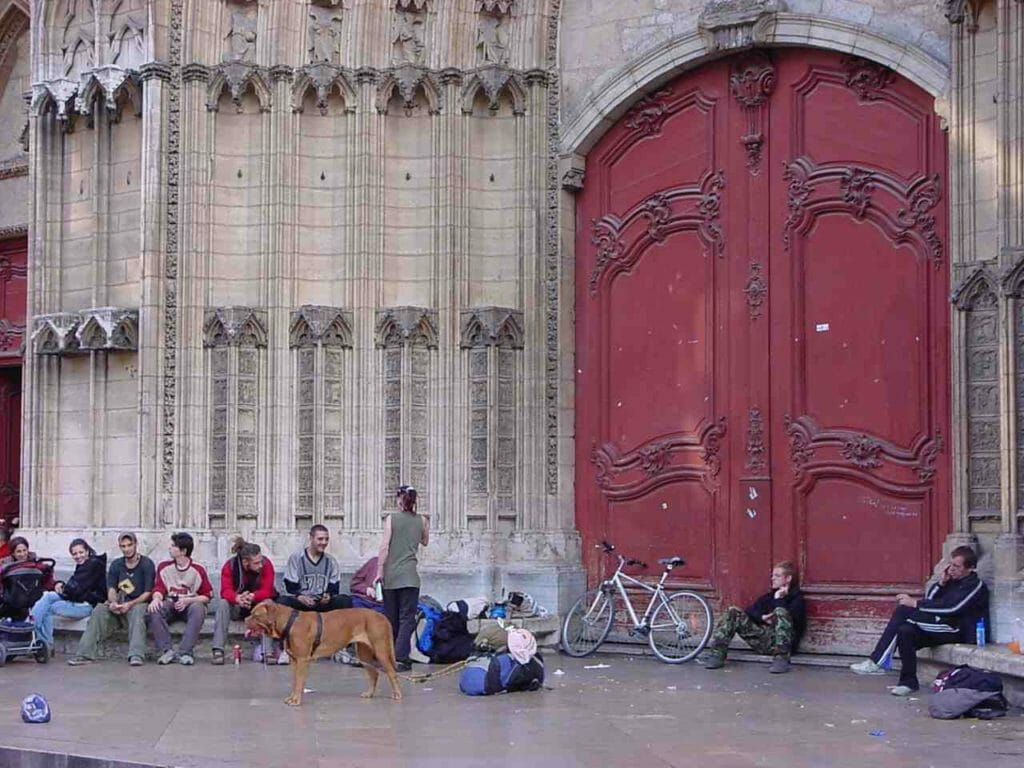 People hanging out in front of a basilica in Lyon, France. One has a large dog, another a bicycle.