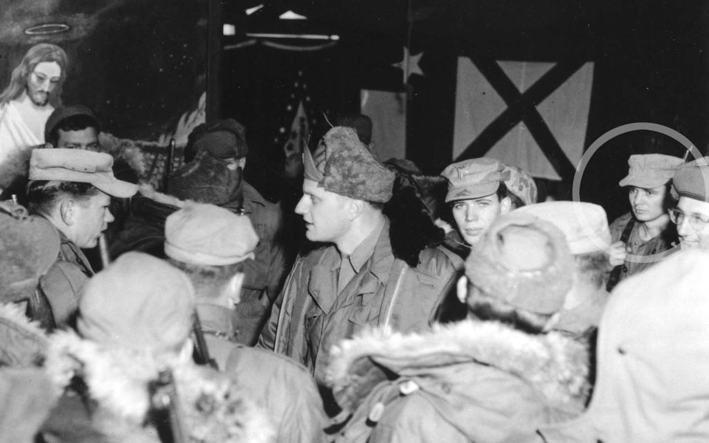 Billy Graham shares the gospel with Marines in the Korean War. Ted Fletcher, at right, listens.