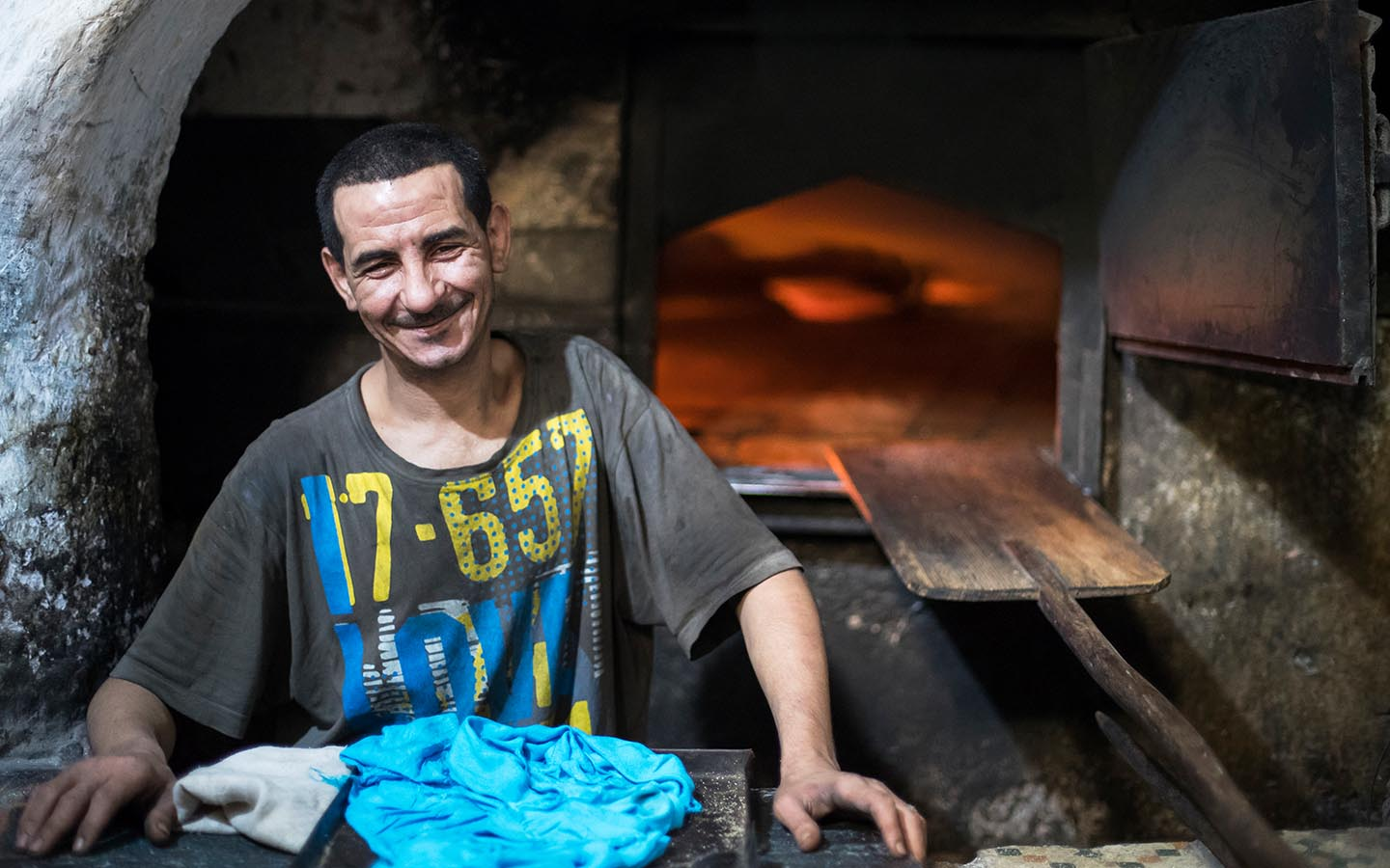smiling baker sells traditional bread