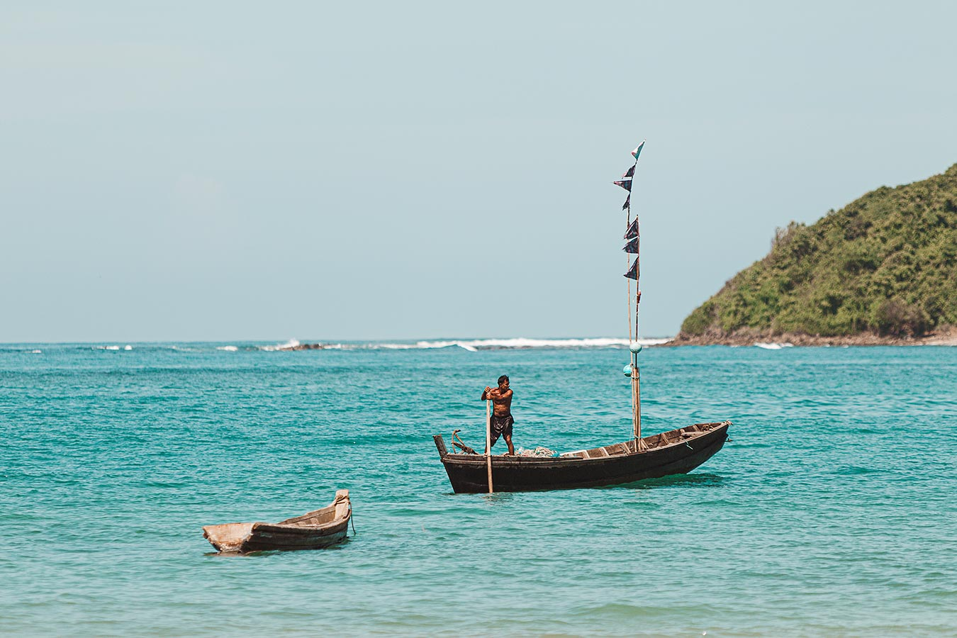 A small fishing boat comes into the harbor - Southeast Asia fishing village