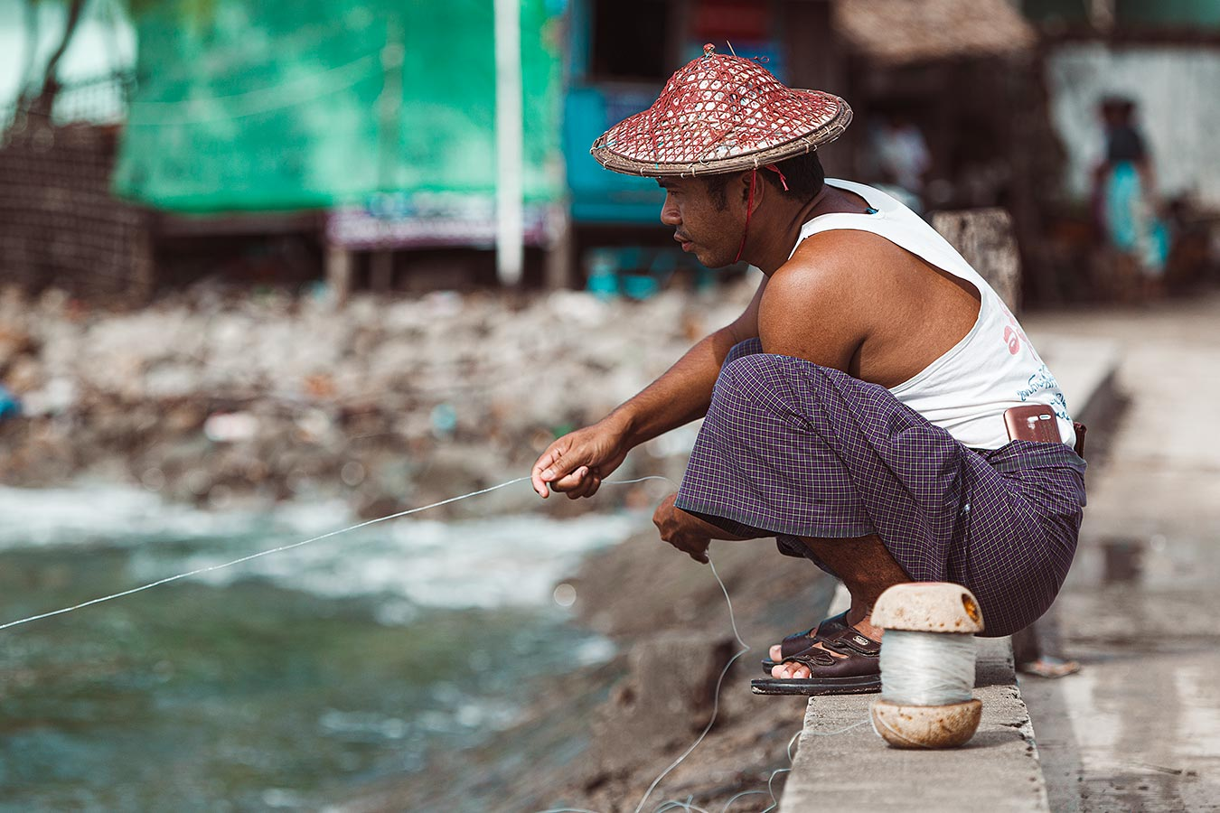 A man fishes for baracuda from a dock in southeast Asia