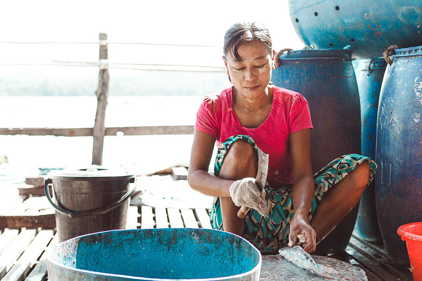 A woman cuts, cleans and salts the daily catch - fishing village in Southeast Asia