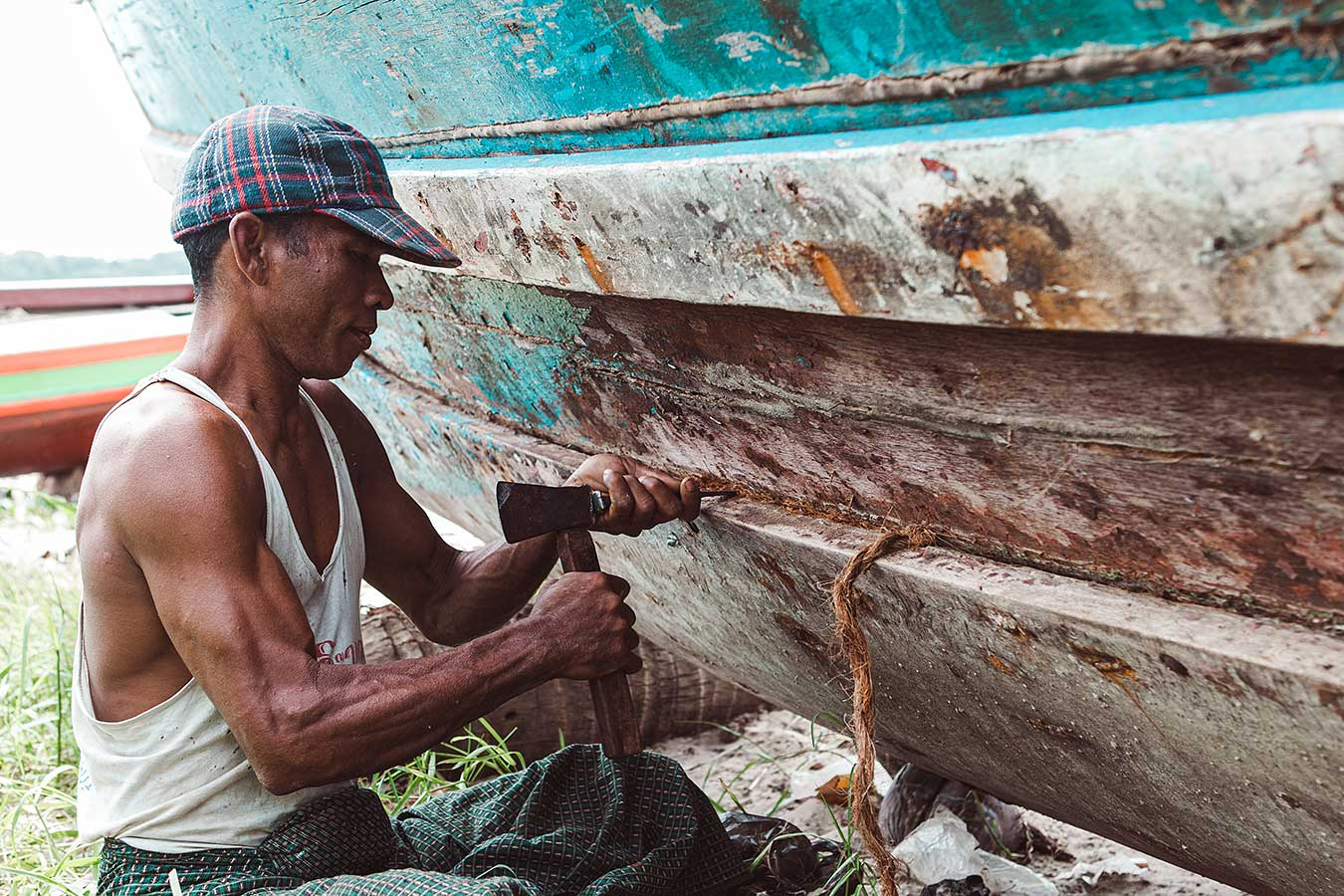 Man repairs his wooden boat with rope - fishing village in Southeast Asia