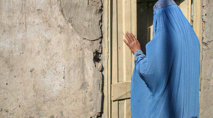 An Afghan woman in a blue burka standing in a doorway